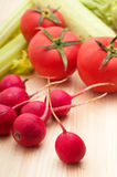 Fresh raddish and vegetables. Fresh   raddish and vegetables over pine wood table closeup Stock Photography