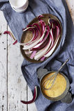 Fresh radicchio treviso quality on tray and cornmeal flour for preparing polenta on table with cloth Royalty Free Stock Photos