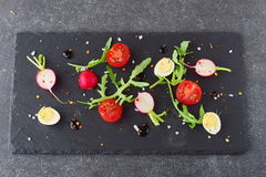 Fresh radish, cherry tomato, quail egg, ruccola with balsamic glaze on a black stone plate. Mediterranean lifestyle. Healthy food Royalty Free Stock Images