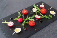 Fresh radish, cherry tomato, quail egg, ruccola with balsamic glaze on a black stone plate. Mediterranean lifestyle Stock Photography