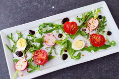 Fresh radish, cherry tomato, quail egg, ruccola with balsamic glaze on a white plate. Mediterranean lifestyle. Healthy. Food Stock Image