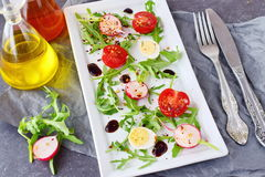 Fresh radish, cherry tomato, quail egg, ruccola with balsamic glaze on a white plate. Mediterranean lifestyle. Healthy. Food Stock Photos