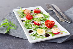 Fresh radish, cherry tomato, quail egg, ruccola with balsamic glaze on a white plate. Mediterranean lifestyle. Healthy. Food Royalty Free Stock Image