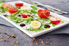 Fresh radish, cherry tomato, quail egg, ruccola with balsamic glaze on a white plate. Mediterranean lifestyle. Healthy. Food. Selective focus Royalty Free Stock Photography