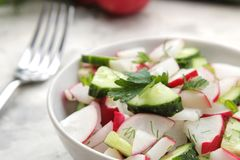 Fresh radish and cucumber salad and greens on a light concrete table. Salad of spring vegetables. ingredients for making salad. Fresh radish and cucumber salad royalty free stock photography
