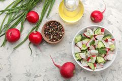 Fresh radish and cucumber salad and greens on a light concrete table. Salad of spring vegetables. ingredients for making salad. to. P view royalty free stock photo
