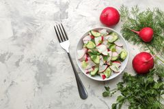 Fresh radish and cucumber salad and greens on a light concrete table. Salad of spring vegetables. ingredients for making salad. to. Fresh radish and cucumber stock photos