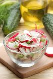 Fresh radish and cucumber salad and greens on a natural wooden table. Salad of spring vegetables. ingredients for making salad royalty free stock image
