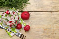 Fresh radish and cucumber salad and greens on a natural wooden table. Salad of spring vegetables. ingredients for making salad. to. P view royalty free stock photos