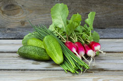 Fresh radish, cucumbers and chives. Radish, cucumbers and chives outdoors on wooden table Royalty Free Stock Photos