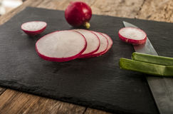 Fresh radish cut in black background. Close up Royalty Free Stock Image
