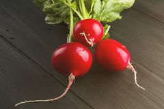 Fresh radish on a dark wooden background. Toning. Royalty Free Stock Photos