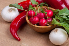 Fresh radish. Es i a wooden bowl with peppers and onions on background Stock Image