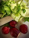 Fresh Radishes and Bok Choy slice on a cutting board. And being prepared for a steak and starry dish Stock Photo
