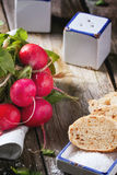 Fresh radishes with bread. Fresh wet radishes with sea salt and bread over old wooden table. See series Stock Photography