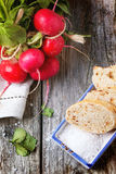 Fresh radishes with bread. Fresh wet radishes with sea salt and bread over old wooden table. Top view Stock Photo