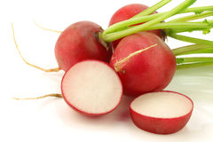 Fresh radishes and a cut one. On a white background Royalty Free Stock Photos