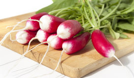 Fresh radishes on a cutting board. Fresh radishes lies on a chopping wooden board Stock Image