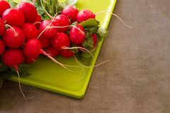 Fresh Radishes on a cutting board on a textured background. Fresh radishes on a cutting boardon a textured background with room for text or copy space Royalty Free Stock Photos