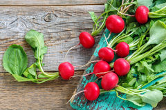 Fresh radishes with green leaves. Radish with green leaves on the old wooden background Stock Photography