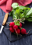 Fresh radishes and knife. Selective focus Royalty Free Stock Photography