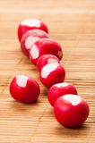 Fresh radishes line up. Red fresh radishes line up on a wooden plate Royalty Free Stock Photography