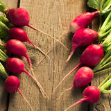 Fresh radishes on old wooden table. Bright fresh radishes on old wooden table Royalty Free Stock Photography