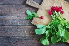 Fresh radishes on old wooden table. Bundle Stock Photo