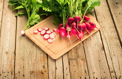 Fresh radishes on old wooden table. Bundle of bright fresh radishes on old wooden table Stock Images