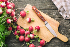 Fresh radishes on old wooden table. Fresh radishes on old cutting board with knife. Healthy vegetable red radishes. Top view Stock Photo