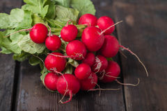Fresh radishes on old wooden table. Fresh radishes on old dark wooden table Stock Photography