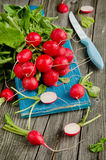 Fresh radishes on old wooden table. Fresh red radishes on old wooden table Stock Images