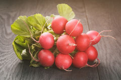 Fresh radishes on old wooden table. Vintage toned Royalty Free Stock Photography