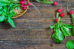 Fresh radishes on old wooden table. In a wicker basket Stock Photo