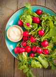 Fresh radishes with pink salt on a plate. Selective focus Stock Image