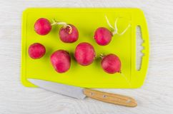 Fresh radishes on plastic cutting board and kitchen knife. On wooden table. Top view Stock Images
