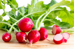 Fresh radishes, Raphanus sativus, on wooden plate. Fresh bunch of radishes, Raphanus sativus, on wooden plate ready to eat or add in healthy salads Stock Images