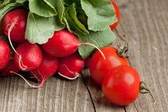 Fresh radishes and tomato Stock Photo