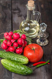 Fresh radishes, tomatoes, cucumbers and olive oil. Old dark wooden table Royalty Free Stock Photo