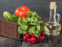 Fresh radishes, tomatoes, cucumbers and olive oil. Old dark wooden table Royalty Free Stock Images