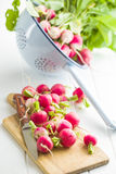 Fresh radishes vegetable. Fresh radishes on old cutting board with knife. Healthy vegetable red radishes Stock Photos
