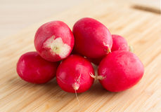 Fresh radishes on a wood cutting board. A group of  fresh radishes on a wood cutting board illuminated with natural light Stock Images
