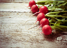 Fresh radishes on wooden background. Toned photo. Selective focus Royalty Free Stock Photos