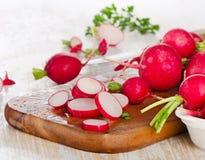Fresh radishes on a  wooden board. Fresh radishes on  a wooden board. Selective focus Stock Photo