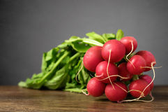 Fresh radishes on wooden table. A bunch of fresh radishes on wooden table Royalty Free Stock Photo