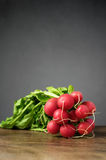 Fresh radishes on wooden table. A bunch of fresh radishes on wooden table Stock Photo