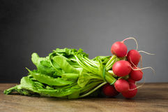 Fresh radishes on wooden table. A bunch of fresh radishes on wooden table Stock Images