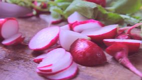 Fresh radishes on wooden table, cutting stock video footage