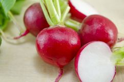 Fresh radishes on a wooden table. Fresh recently washed  radishes on a wooden table close up Royalty Free Stock Images