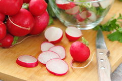 Fresh radishes on wooden table. Fresh sliced radishes on wooden table Royalty Free Stock Photos